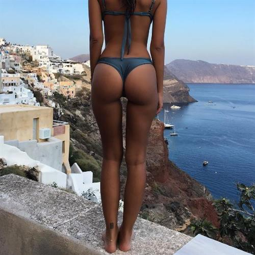 Emily Ratajkowski  is standing on a wall watching the sea and exposing her delicious ass.
