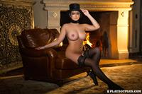 Playboy Cybergirl Chelsie Aryn poses in front of a fire place wearing a top hat