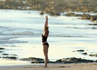 Miley Cyrus  yoga in black bikini on beach in Hawaii 1/24/13