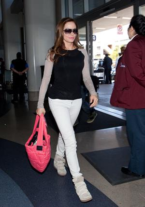 Rose McGowan - Prepares to depart LAX carrying a pink handbag - June 6, 2012